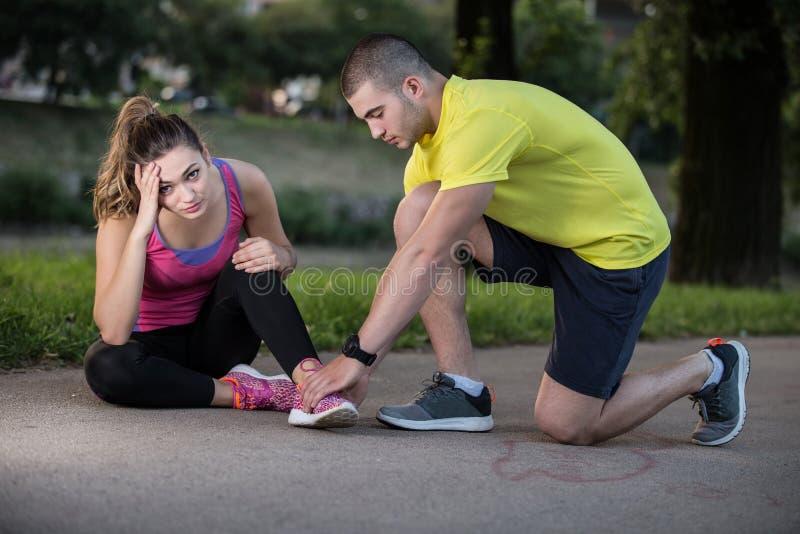 Βοήθειες ανδρών στη γυναίκα με το τραυματισμένο γόνατο στην αθλητική δραστηριότητα στοκ εικόνα