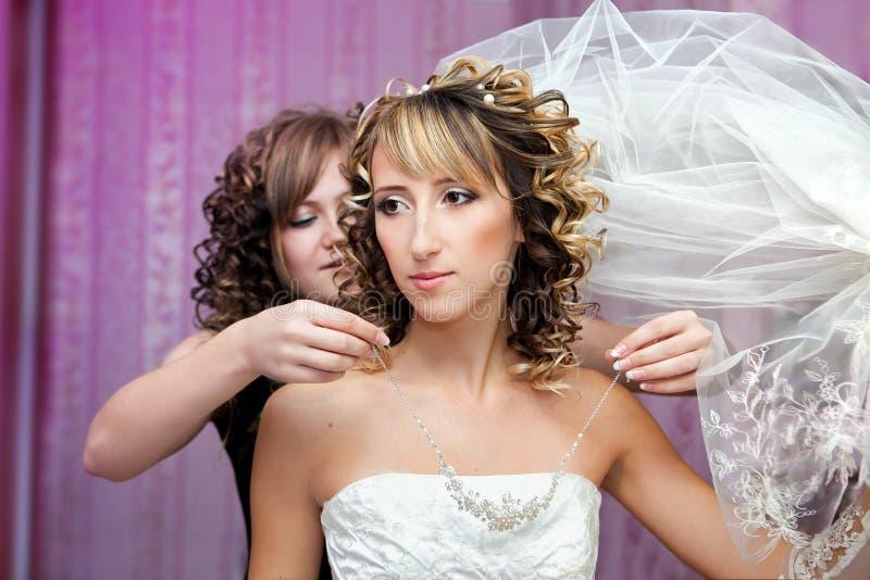 Βοήθειες παράνυμφων στη νύφη για να βάλει στο κόσμημα στοκ εικόνες