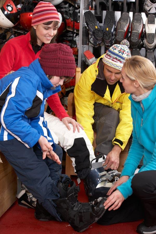 Βοηθητική βοηθώντας οικογένεια πωλήσεων για να προσπαθήσουν στις μπότες σκι στοκ εικόνα