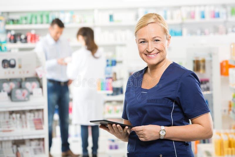 Βοηθητική ψηφιακή ταμπλέτα εκμετάλλευσης στο φαρμακείο στοκ εικόνες με δικαίωμα ελεύθερης χρήσης