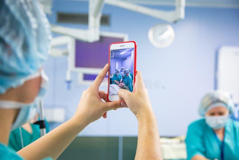 Βοηθητικός πυροβολισμός στο smartphone από το λειτουργούν δωμάτιο Ιατρική ομάδα που εκτελεί τη χειρουργική λειτουργία σε σύγχρονο στοκ εικόνες με δικαίωμα ελεύθερης χρήσης