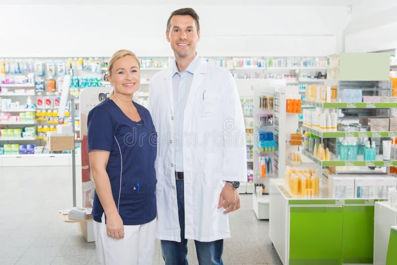 Βοηθός και φαρμακοποιός που στέκονται στο φαρμακείο στοκ φωτογραφία