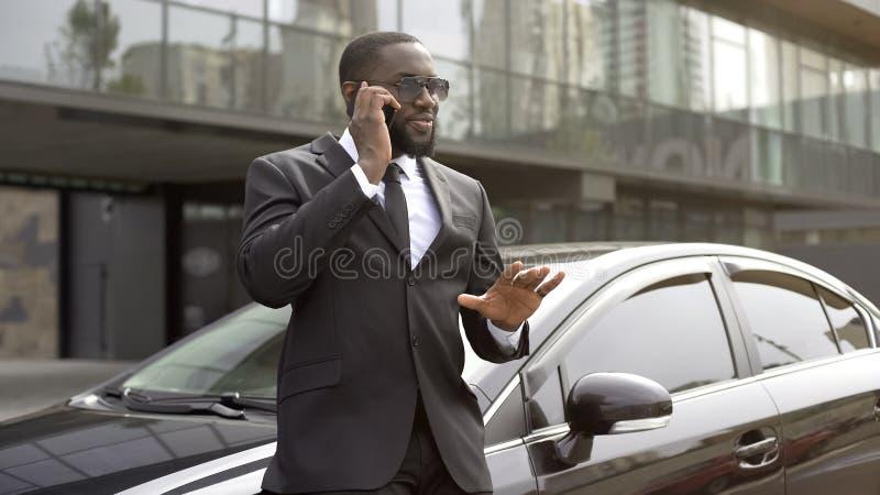 Βοηθός που ηρεμεί κάτω τον προϊστάμενό του με τηλέφωνο που μιλά για την καλή έκβαση της συνεδρίασης στοκ φωτογραφία