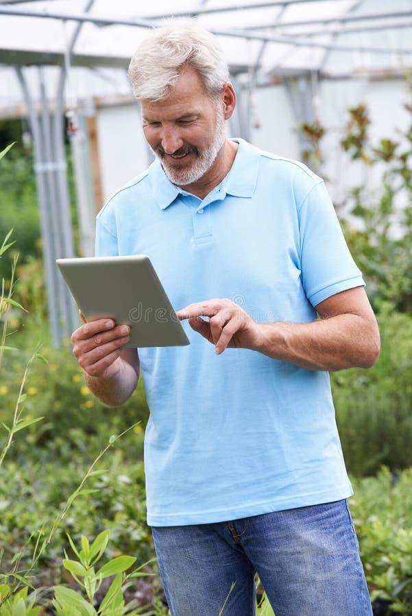 Βοηθός πωλήσεων στο κέντρο κήπων με την ψηφιακή ταμπλέτα στοκ φωτογραφία με δικαίωμα ελεύθερης χρήσης