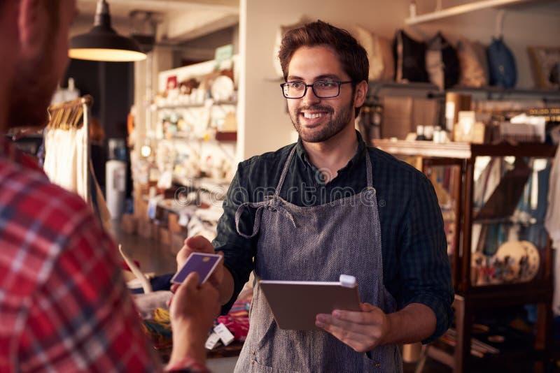 Βοηθός πωλήσεων με τον αναγνώστη πιστωτικών καρτών στην ψηφιακή ταμπλέτα στοκ φωτογραφίες
