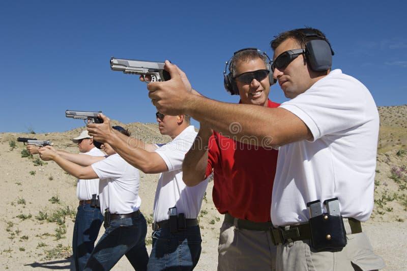 Βοηθώντας ανώτεροι υπάλληλοι εκπαιδευτικών με τα πυροβόλα όπλα χεριών στη σειρά πυρκαγιών στοκ φωτογραφίες με δικαίωμα ελεύθερης χρήσης