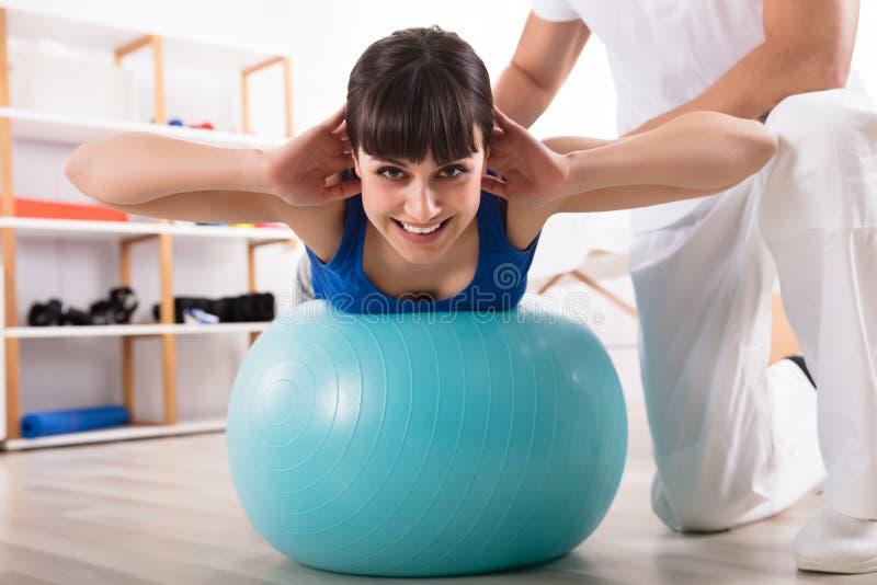 Βοηθώντας γυναίκα φυσιοθεραπευτών κάνοντας την άσκηση στοκ φωτογραφία