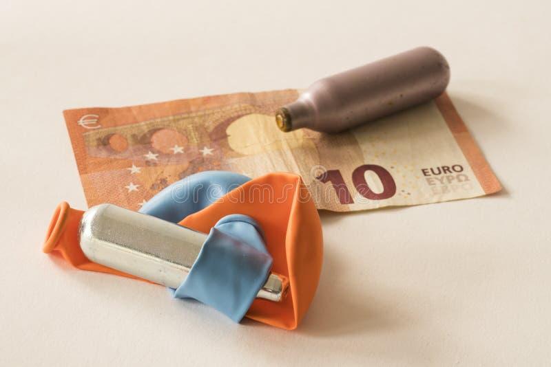 Βολβοί και μπαλόνια μετάλλων για το αέριο γέλιου, με δέκα ευρώ στοκ εικόνες