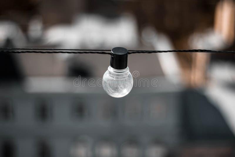 Βολβός γυαλιού με τη μαύρη βάση στο υπόβαθρο των σπιτιών Λάμπα φωτός επάνω r o στοκ φωτογραφίες με δικαίωμα ελεύθερης χρήσης