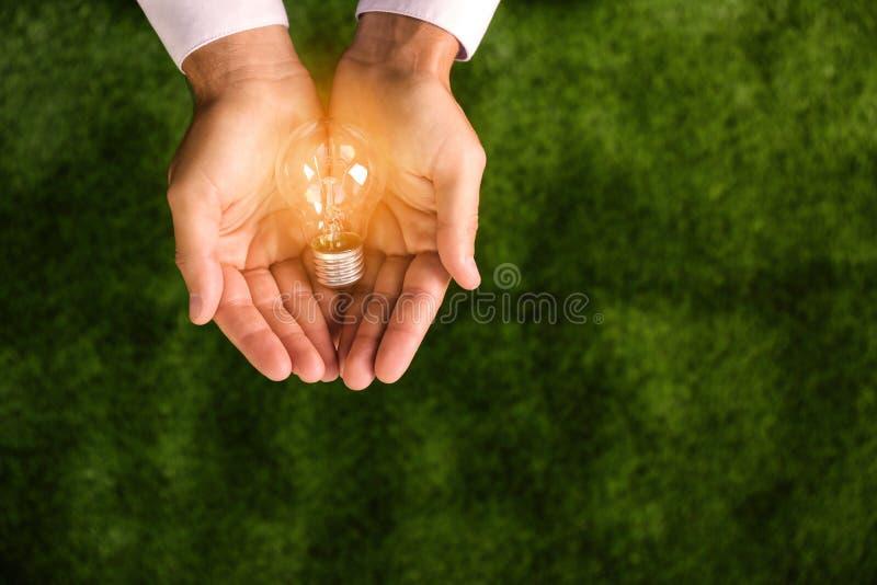 Βολβός λαμπτήρων εκμετάλλευσης ατόμων στο πράσινο κλίμα, τοπ άποψη στοκ εικόνες