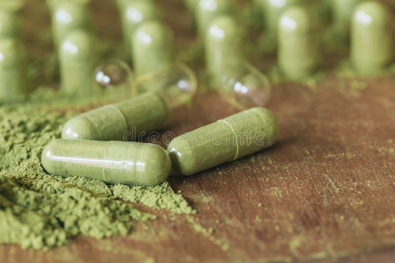 Βοτανική ιατρική στις κάψες με τα πράσινα χορτάρια σκονών στοκ εικόνα