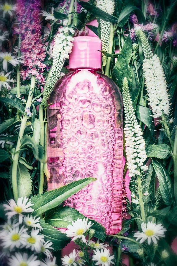 Βοτανικό ή floral καλλυντικό μπουκάλι προϊόντων στο υπόβαθρο χορταριών και λουλουδιών, τοπ άποψη Skincare, wellness, φυσικό καλλυ στοκ εικόνα