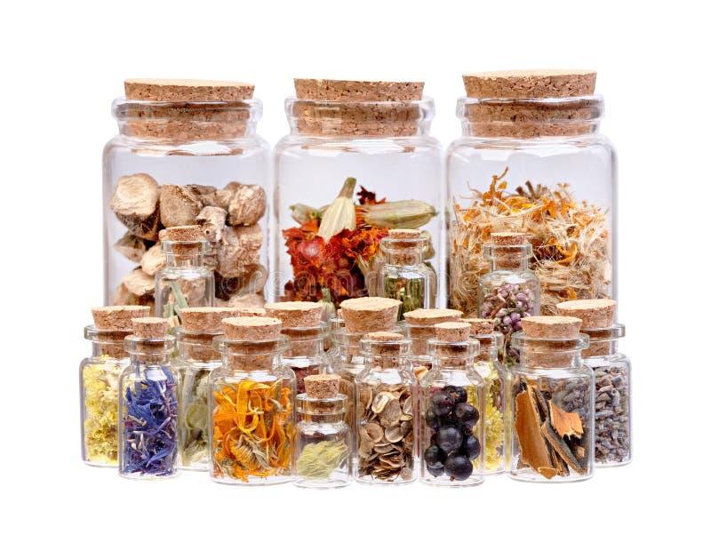 Βοτανικό τσάι, ξηρά χορτάρια, λουλούδια και μούρα στα μπουκάλια FO γυαλιού στοκ εικόνα