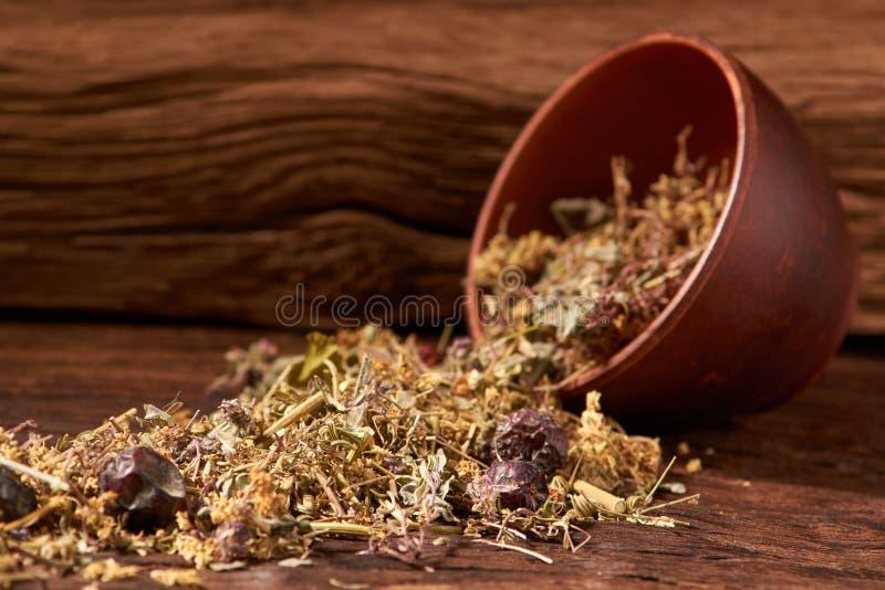 βοτανικό τσάι στο κύπελλο αργίλου στον ξύλινο πίνακα στο μαύρο υπόβαθρο Εκλεκτική εστίαση στοκ εικόνα
