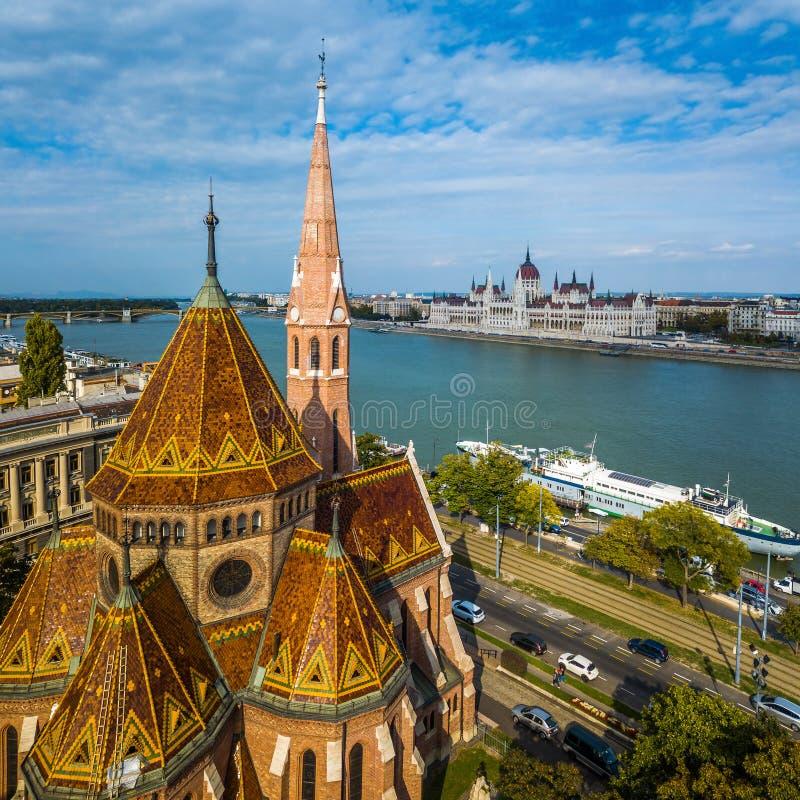 Βουδαπέστη, Ουγγαρία - εναέρια άποψη της ανασχηματισμένης εκκλησίας στην πλατεία Szilagyi Dezso με το ουγγρικό Κοινοβούλιο στοκ φωτογραφία με δικαίωμα ελεύθερης χρήσης