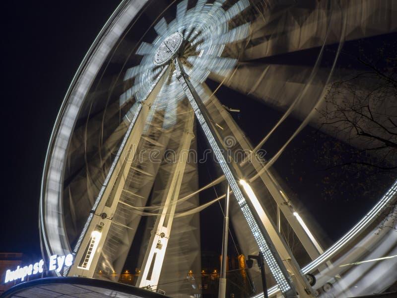 Βουδαπέστη, Ουγγαρία Η ρόδα Ferris που φωτίζεται στο λευκό το βράδυ Τα φω'τα δημιουργούν τα άσπρα λωρίδες στοκ φωτογραφία με δικαίωμα ελεύθερης χρήσης