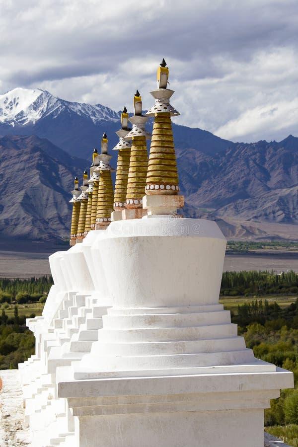 Βουδιστικά chortens, άσπρα stupa και βουνά των Ιμαλαίων στο υπόβαθρο κοντά στο παλάτι Shey σε Leh σε Ladakh, Ινδία στοκ εικόνα