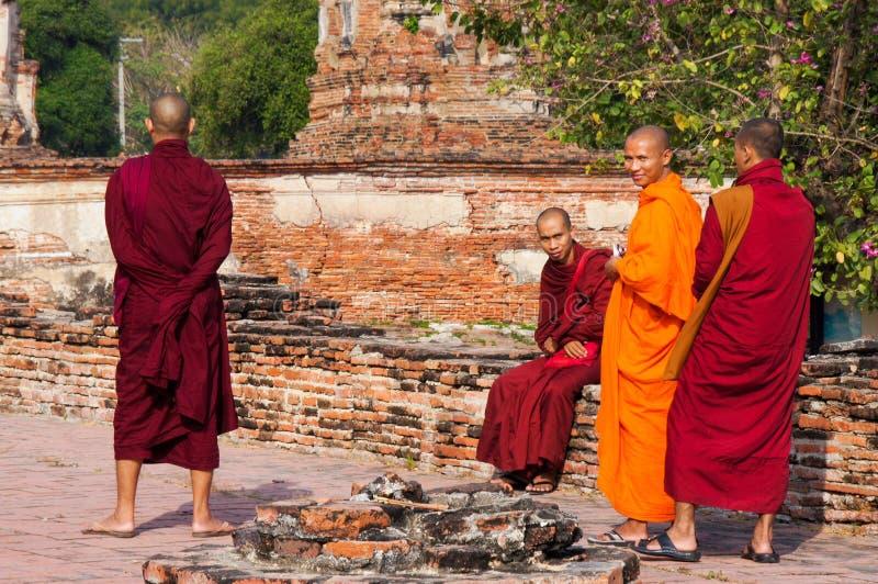 Βουδιστικοί μοναχοί στις μακριές τηβέννους που περπατούν στο πάρκο στην Ταϊλάνδη στοκ εικόνα