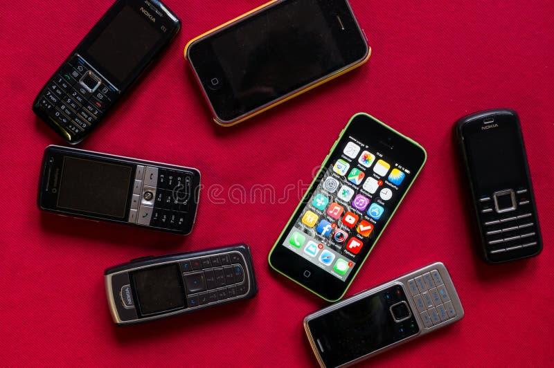 ΒΟΥΚΟΥΡΕΣΤΙ, ΡΟΥΜΑΝΙΑ - 17 ΜΑΡΤΊΟΥ 2014: Φωτογραφία του iphone εναντίον των παλαιών τηλεφώνων της Nokia σε ένα κόκκινο υπόβαθρο π στοκ εικόνα με δικαίωμα ελεύθερης χρήσης
