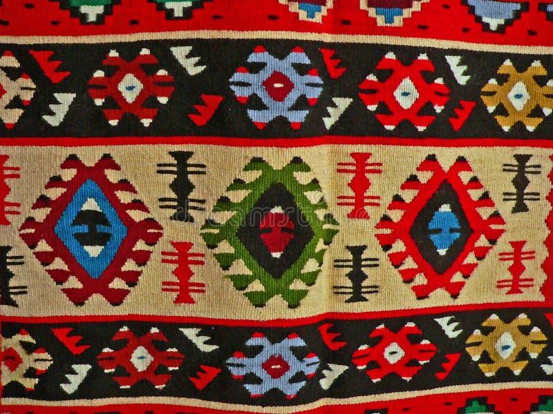 Βουλγαρικό παραδοσιακό λαϊκό ύφασμα ταπήτων με τα γεωμετρικά κίνητρα και τα φωτεινά χρώματα στοκ φωτογραφίες