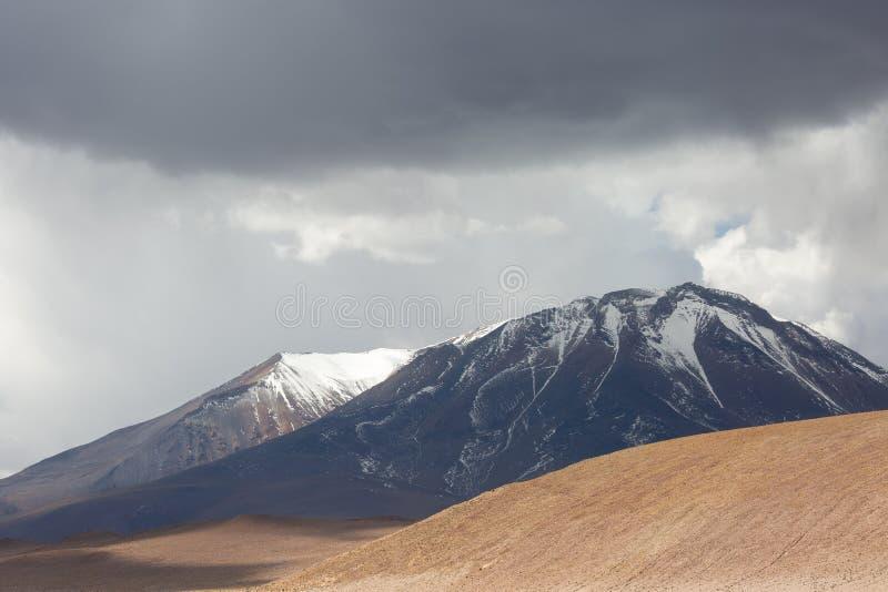 Βουνά, θυελλώδεις ουρανοί και βροχερά σύννεφα στο βολιβιανό Andest στοκ εικόνα