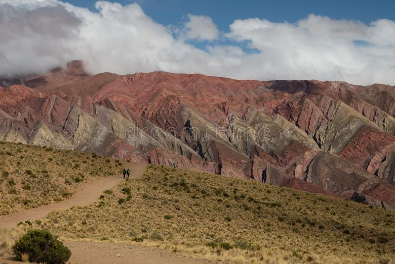 Βουνά και κοιλάδα ουράνιων τόξων σε Humahuaca Αργεντινή με τους οδοιπόρους στοκ εικόνες
