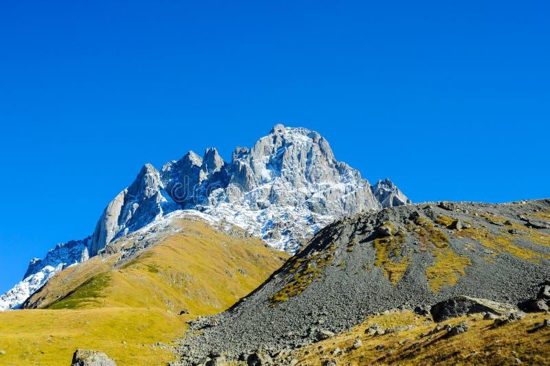 Βουνά Καύκασου το καλοκαίρι, μέγιστους Chiukhebi και το μπλε ουρανό στοκ φωτογραφία