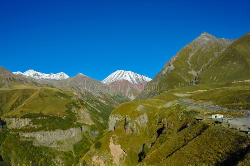 Βουνά Καύκασου το καλοκαίρι, τους πράσινους λόφους, το μπλε ουρανό και χιονώδες μέγιστο Mkinvari δρόμος από Gudauri σε Stepantsmi στοκ φωτογραφίες