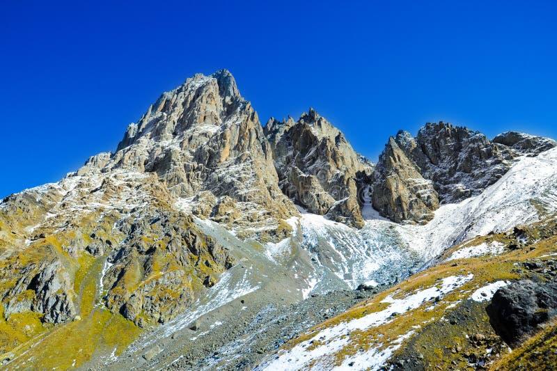 Βουνά Καύκασου, χωριό Juta πράσινος λόφος, μπλε ουρανός, και χιονώδες μέγιστο Chaukhebi το καλοκαίρι στοκ εικόνα