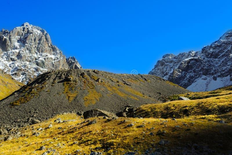 Βουνά Καύκασου, χωριό Juta πράσινος λόφος, μπλε ουρανός, και χιονώδες μέγιστο Chaukhebi το καλοκαίρι στοκ εικόνες με δικαίωμα ελεύθερης χρήσης