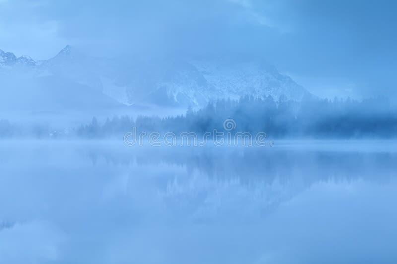 Βουνά που απεικονίζονται στη λίμνη στην πυκνή ομίχλη στοκ φωτογραφία