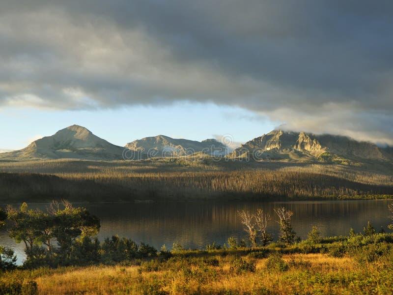 Βουνά που απεικονίζονται στη λίμνη στο εθνικό πάρκο παγετώνων ανατολής στοκ εικόνα