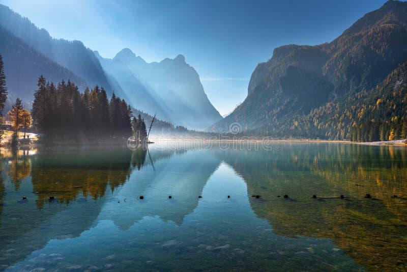 Βουνά που απεικονίζονται στο νερό στην όμορφη λίμνη στο ηλιόλουστο πρωί στοκ φωτογραφίες