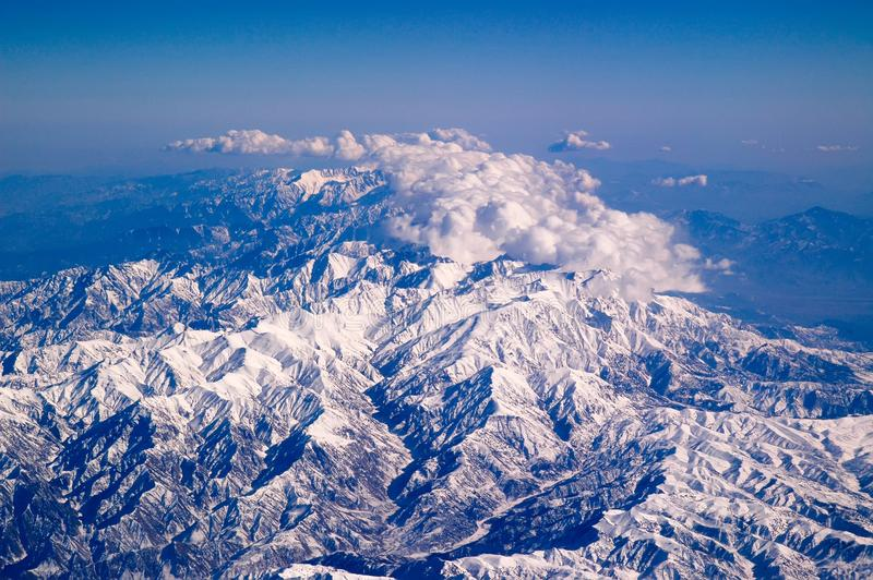 Βουνά που καλύπτονται με το χιόνι και τα σύννεφα, εναέρια άποψη Επιφάνεια γήινων πλανητών Ταξίδι σε όλο τον κόσμο περιβάλλον στοκ εικόνες