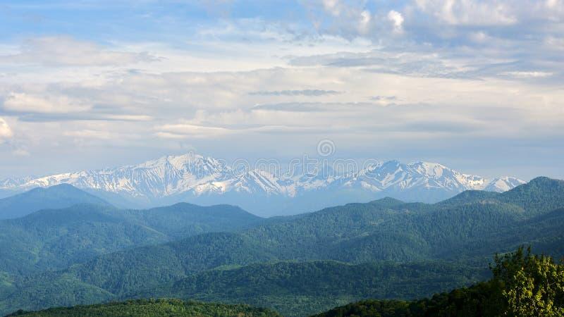 Βουνά του βόρειου Καύκασου στο ηλιοβασίλεμα Χιονοσκεπείς αιχμές στον ήλιο στοκ εικόνα με δικαίωμα ελεύθερης χρήσης