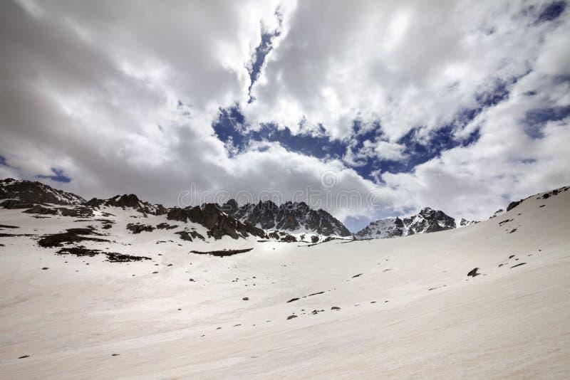 Βουνό χιονιού και ουρανός σύννεφων στην γκρίζα ημέρα άνοιξη στοκ φωτογραφίες