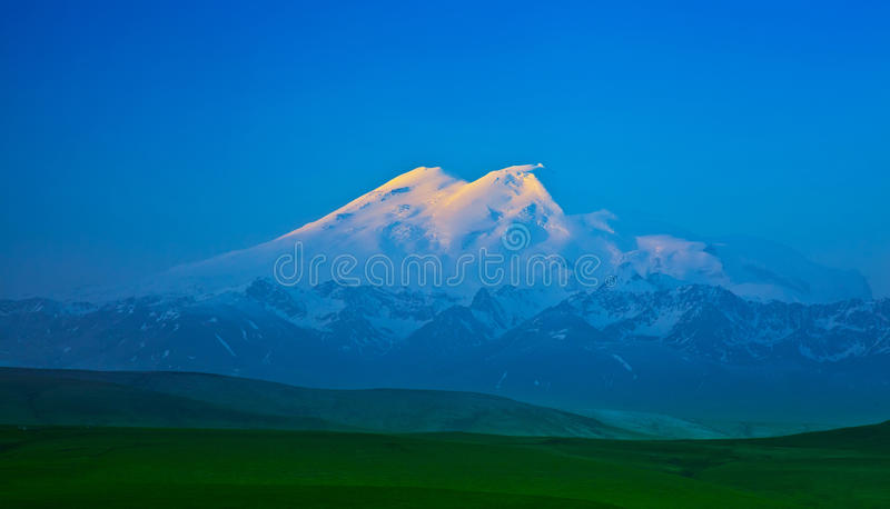 Βουνό Elbrus αναμμένο από τις ακτίνες του ήλιου αύξησης στοκ εικόνες