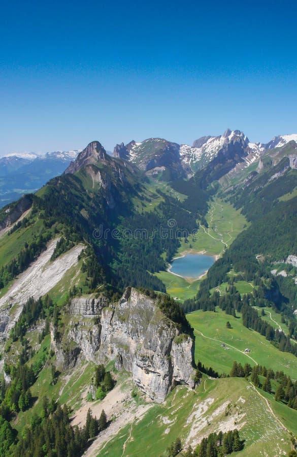 Βουνό landcape στις ελβετικές Άλπεις με τις οδοντωτές αιχμές και μια παλιή μπλε λίμνη βουνών στην κοιλάδα μακριά κατωτέρω στοκ εικόνα