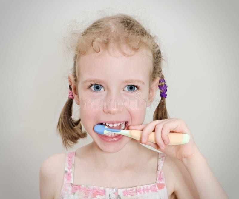 βουρτσίζοντας το κορίτσι αυτή μικρά δόντια στοκ εικόνες