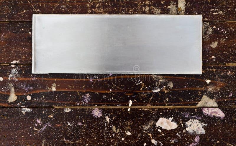 Βουρτσισμένο αλουμίνιο πιάτο στο ξύλο με το σημείο των χρωμάτων στοκ φωτογραφίες
