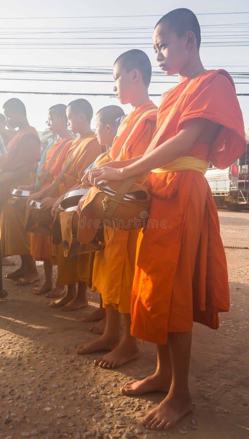 Βουδιστικοί αρχάριοι που περιμένουν τα τρόφιμα που προσφέρουν το πρωί στοκ εικόνες