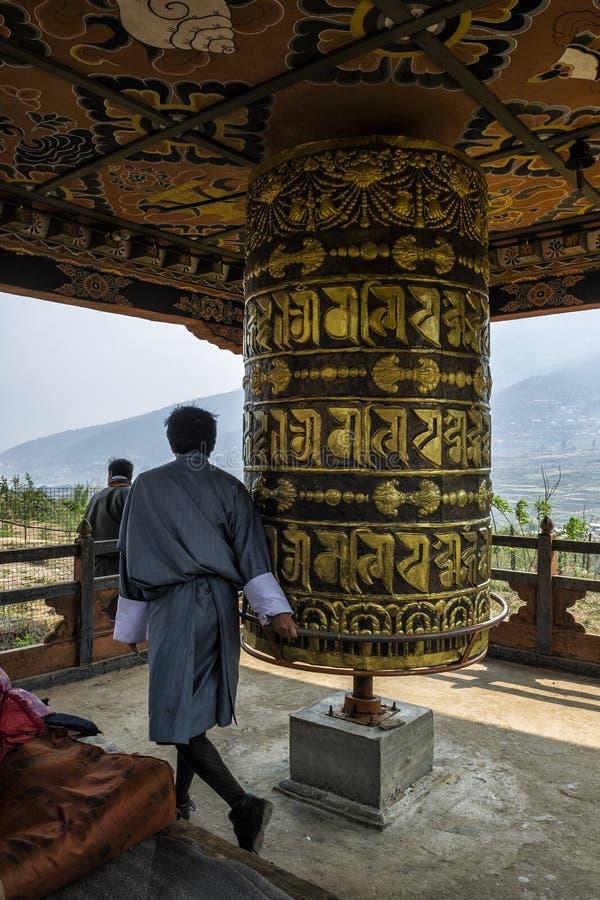 Βουδιστικός προσκυνητής που προσεύχεται με μια ρόδα προσευχής στο μοναστήρι Chimi Lhakang, Μπουτάν στοκ εικόνα