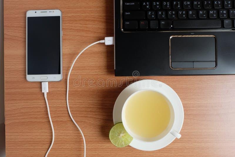 Βούλωμα στο φορτιστή σκοινιού USB του κινητού τηλεφώνου με ένα lap-top και πρόσφατα χυμός ασβέστη σε ένα άσπρο φλυτζάνι, στο ξύλι στοκ εικόνες