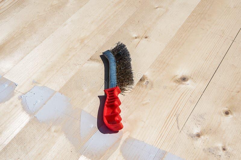 Βούρτσα για το μέταλλο με μια κόκκινη λαβή στοκ φωτογραφία με δικαίωμα ελεύθερης χρήσης