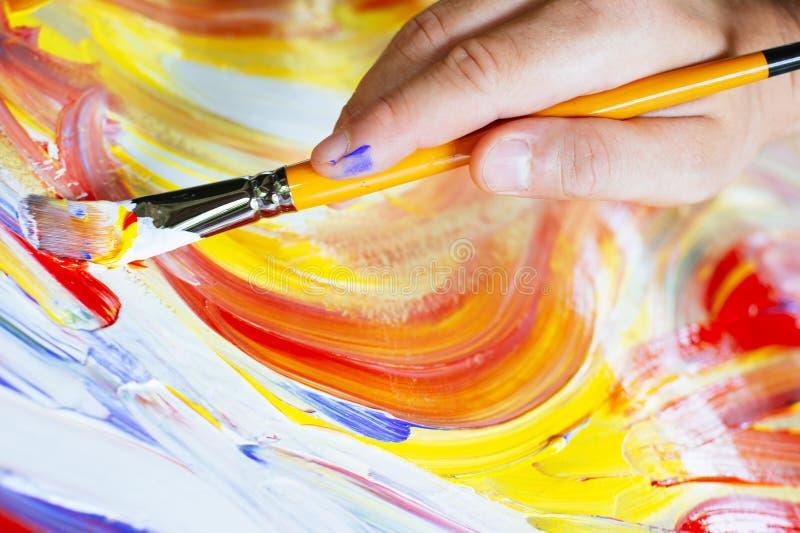 Βούρτσα εκμετάλλευσης χεριών και ζωγραφική με τα ακρυλικά χρώματα στοκ εικόνα