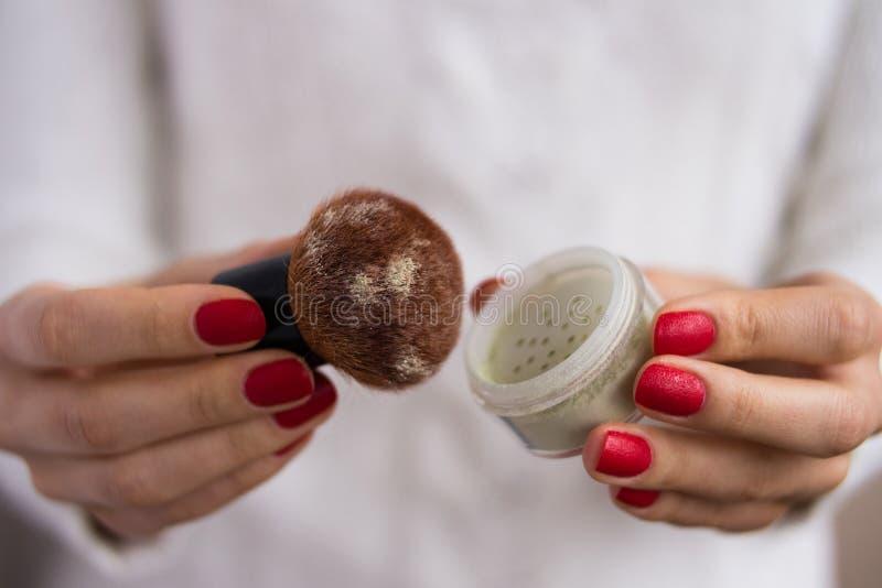 Βούρτσα και σκόνη στα θηλυκά χέρια στοκ φωτογραφία