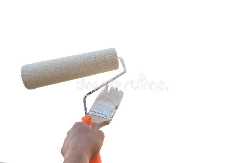 Βούρτσα κυλίνδρων χρωμάτων εκμετάλλευσης χεριών που απομονώνεται σε ένα άσπρο υπόβαθρο στοκ φωτογραφίες