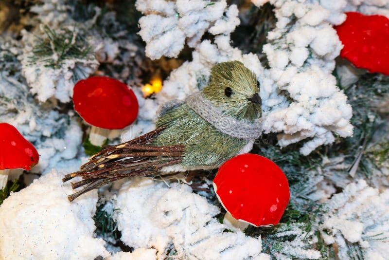 Βούρτσα σκληρών τριχών και πουλί ραβδιών με το πλεκτό μαντίλι στο συγκεντρωμένο χριστουγεννιάτικο δέντρο με τα φωτεινά κόκκινα μα στοκ φωτογραφίες με δικαίωμα ελεύθερης χρήσης
