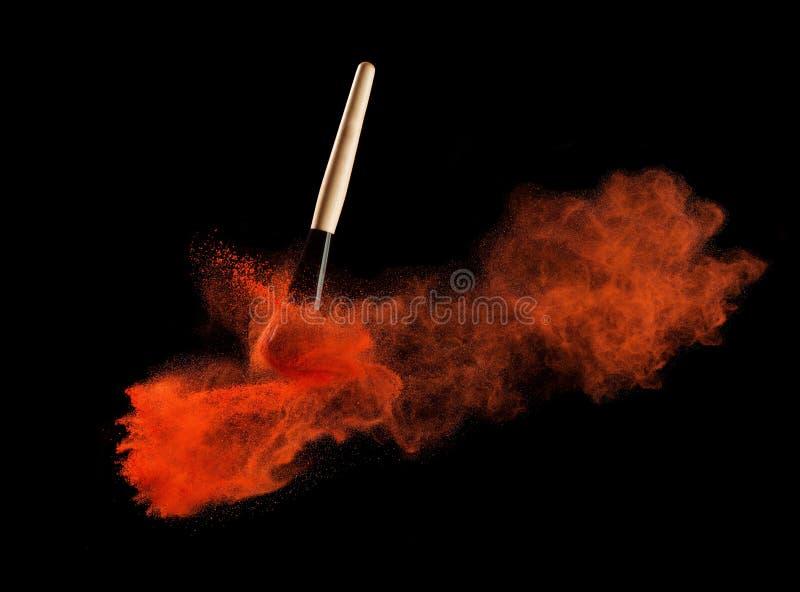 Βούρτσα σύνθεσης με την έκρηξη redpowder στο μαύρο υπόβαθρο στοκ εικόνες