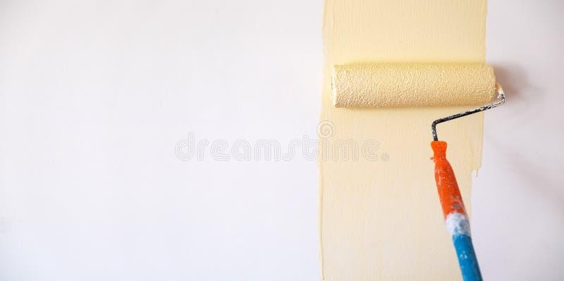 Βούρτσα χρωμάτων κυλίνδρων που χρωματίζει το ανοικτό κίτρινο χρώμα στη λευκιά ΤΣΕ τοίχων στοκ φωτογραφία με δικαίωμα ελεύθερης χρήσης